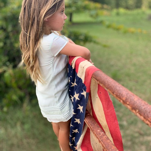 Remi watches her horses and goats on a hot July afternoon. The gate was so hot it was burning her feet so we used an old American flag to keep the gate from scorching her! —Buffy McKenzie, Ellerbe, Pee Dee Electric