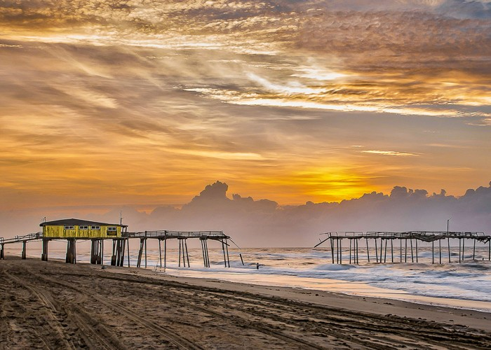 The bygone Frisco Pier was captured at sunrise on a cool March morning along the vast Outer Banks beaches. Taking these photos preserves history and rejuvenates the memories her visitors. —Kenneth Newman, Prince George, VA, Cape Hatteras Electric