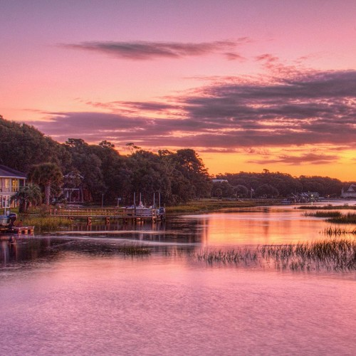 During this Sunset Beach sunrise on a cool October morning, the Intra-Coastal Waterway reflected the magenta sky, and the sun reflecting on the windows of the house gave off a brilliant golden glow. —Michelle Tinger, Sunset Beach, Brunswick Electric