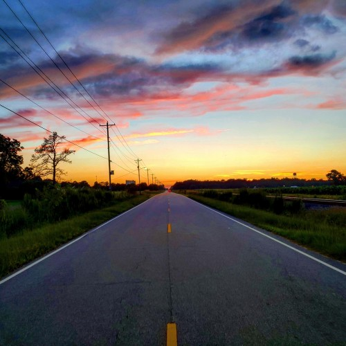 Sunset falls on Anaconda Road in Tarboro. The colors combined with the power lines, railroad tracks, farm fields and the water tower in the distance make up this classic Edgecombe County scene. —Robert Womble, Bryson City